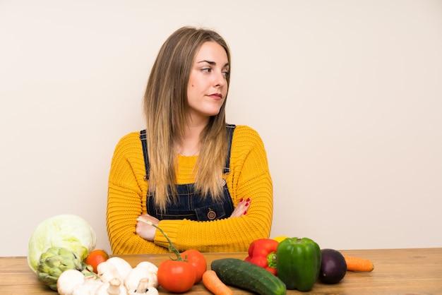Femme avec beaucoup de légumes debout et pensant une idée