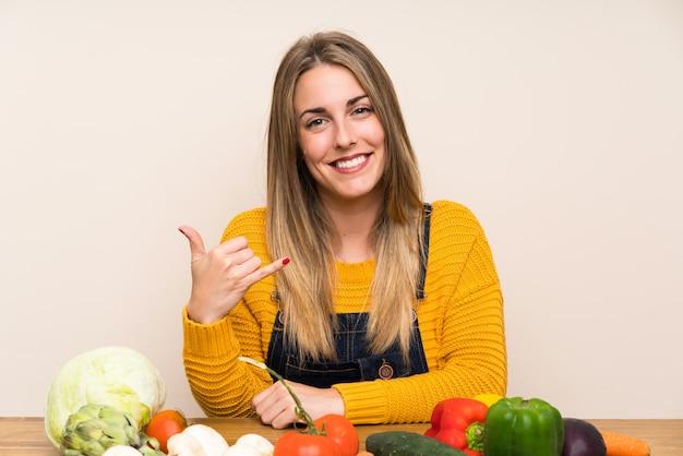 Femme avec beaucoup de légumes faisant un geste de téléphone