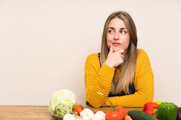Femme avec beaucoup de légumes pense à une idée