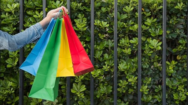 Femme avec beaucoup de sacs shopping lumineux près des plantes