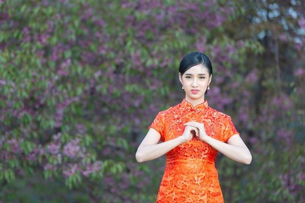 Femme de beauté asiatique avec geste de félicitation au nouvel an chinois