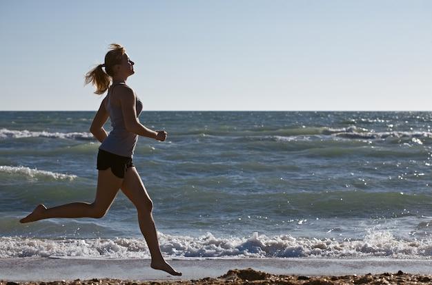 Femme de beauté courir sur la plage de la mer