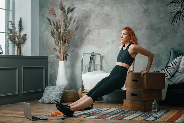 La femme de beauté fait du sport à la maison. femme sportive joyeuse aux cheveux rouges secoue les biceps, faire des pompes sur des boîtes et des montres dans un ordinateur portable, shootting blog dans la chambre