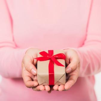 Femme beauté mains tenant petit paquet cadeau boîte présente papier emballé avec ruban