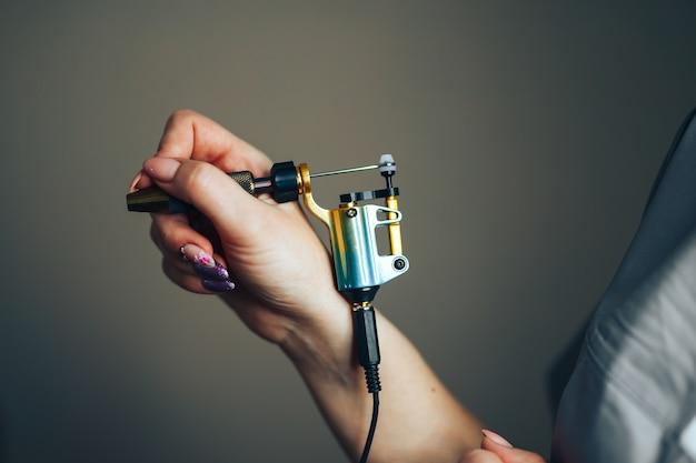 Femme beauté maître tenir l'aiguille pour tatouage-maquillage permanent les mains dans des gants noirs