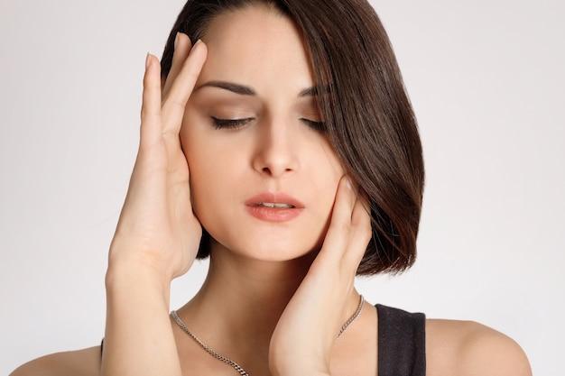 Femme de beauté métisse avec une peau parfaitement saine portrait beau modèle brune touchant le visage