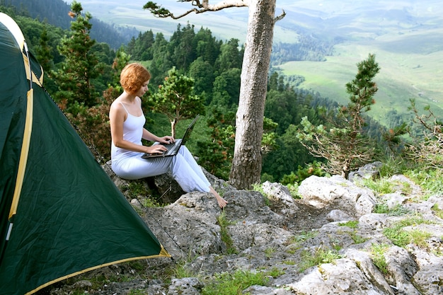 Femme de beauté avec ordinateur portable sur la nature