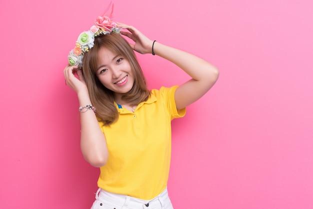 Femme de beauté posant avec un chapeau de fleurs en face de fond de mur rose