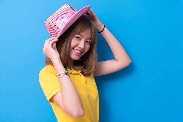 Femme de beauté posant avec un chapeau rose en face de fond de mur bleu
