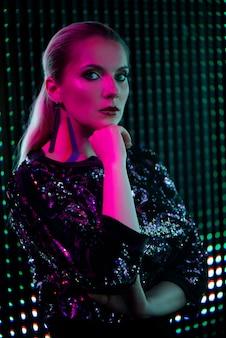 Femme de beauté sexy posant au cours de la nuit ville dramatique fond néon rouge et bleu