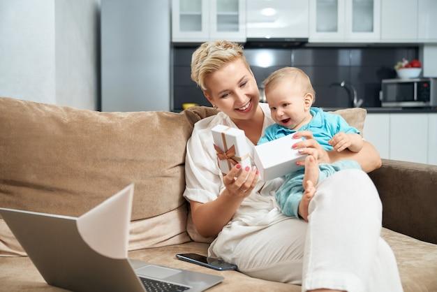 Femme avec bébé assis sur le canapé et cadeau d'ouverture