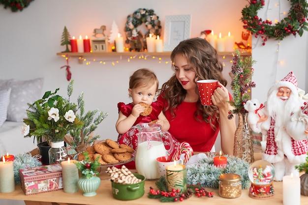 Femme avec bébé dans la cuisine décorée pour noël.