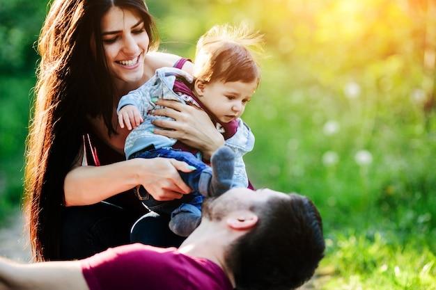 Femme avec un bébé dans ses bras pendant que son copain regarde