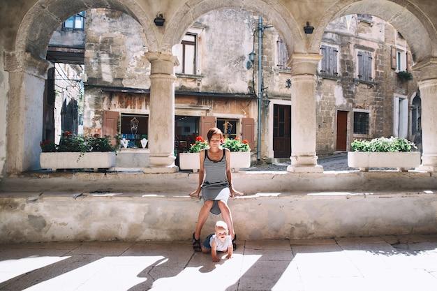 Femme et bébé dans la ville historique de groznjan croatie mère avec enfant sur la vieille rue européenne