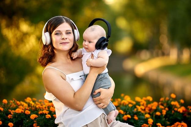 Une femme avec un bébé écoute de la musique avec des écouteurs sans fil à l'extérieur