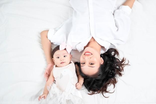 Femme avec un bébé faisant un selfie allongé sur un plancher en bois