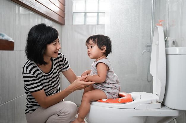 Femme et bébé merde avec fond de toilettes dans la salle de bain