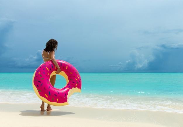 Femme avec beignet gonflable sur la plage