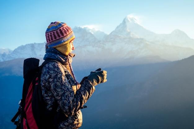 Une femme belle et active tient une tasse avec une boisson chaude dans ses mains. le concept de loisirs actifs et de tourisme en montagne. trekking au népal himalaya.