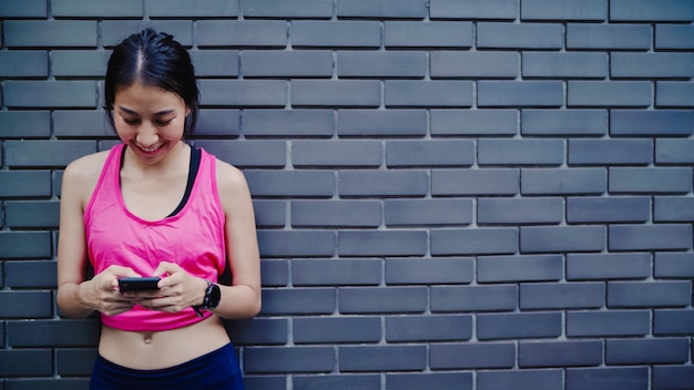 Femme belle athlète asiatique en bonne santé à l'aide de smartphone pour vérifier les médias sociaux