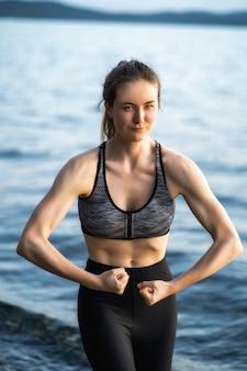 Une femme belle et gonflée montre ses muscles gonflés sur ses bras en se tenant debout sur la rive du lac un soir d'été