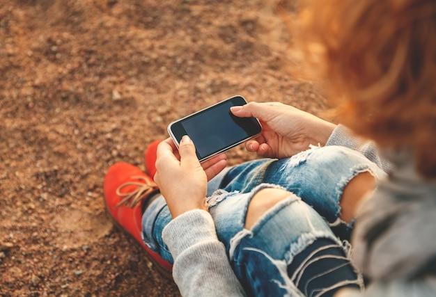 Femme belle jeune hipster à l'aide de téléphone intelligent à la plage