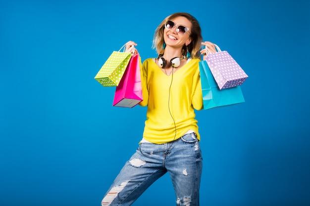 Femme belle jeune hipster, tenant des sacs en papier coloré