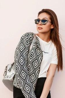 Femme belle jeune mannequin en lunettes de soleil mode avec une veste noire et blanche élégante avec sac à dos posant près du mur rose