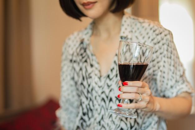 Femme avec une belle manucure rouge tenant un verre de vin rouge.