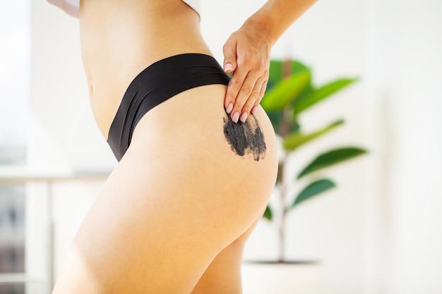 Une femme avec une belle peau applique une crème de gommage anti-cellulite sur ses fesses