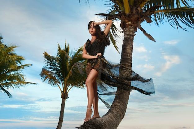 Femme en belle robe avec imprimé léopard sur la plage