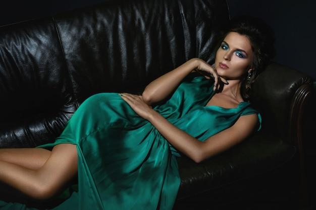Femme en belle robe verte posant sur un canapé en cuir