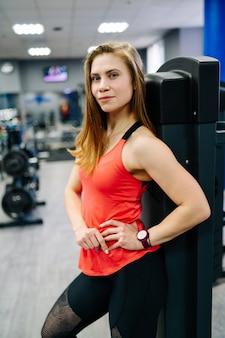 Femme avec une belle silhouette dans la salle de gym près de l'équipement de boxe. tee-shirt orange.