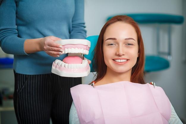 Femme avec de belles dents blanches, assis sur un fauteuil dentaire.