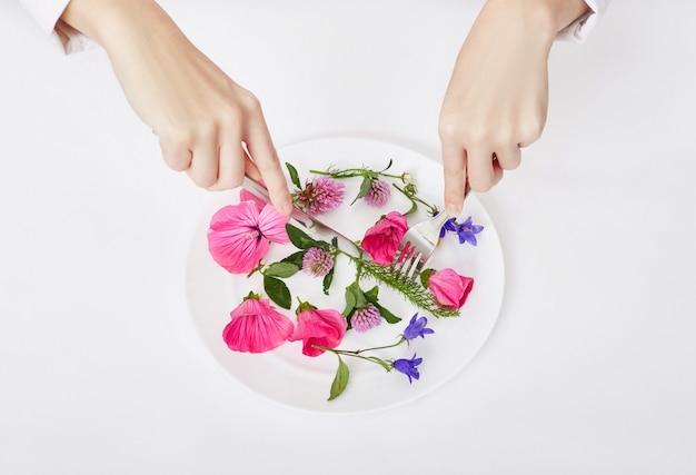 Femme et belles fleurs de printemps dans l'assiette, les mains et les soins de la peau, cosmétique naturelle, extrait de fleur d'été