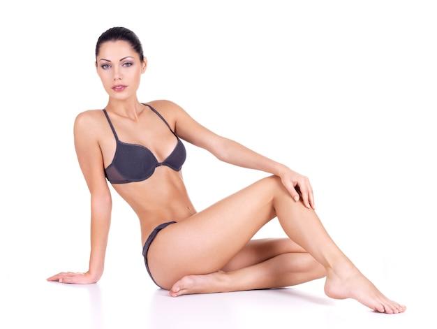Femme avec de belles longues jambes minces en bikini est assise sur fond blanc