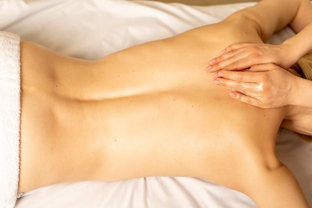 Femme bénéficiant d'un massage relaxant du dos dans le centre de spa cosmétologie