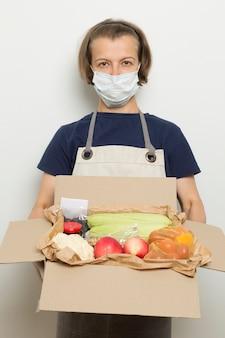 Une femme bénévole dans un masque tient une boîte d'épicerie dans ses mains.