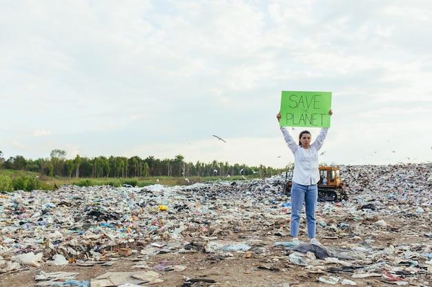 Femme bénévole à la décharge tenant une affiche sauver la terre