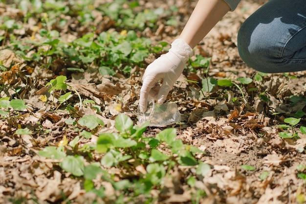 Une femme bénévole est nettoyée dans la forêt une femme ramasse du plastique