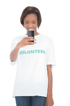 Femme bénévole heureuse en utilisant son téléphone portable