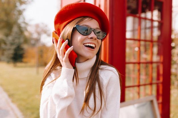 Femme en béret rouge avec parler au téléphone dans la rue