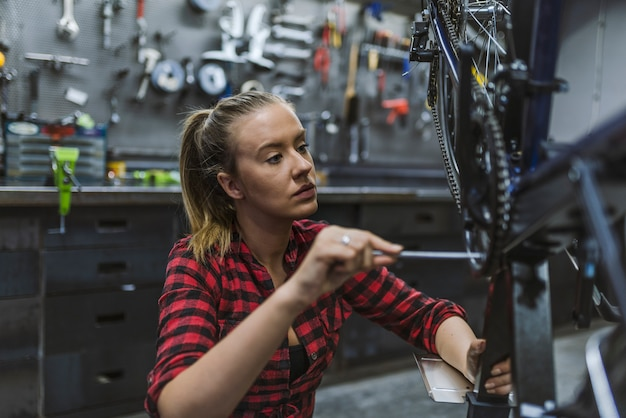 Femme bicyclette répare un vélo dans l'atelier