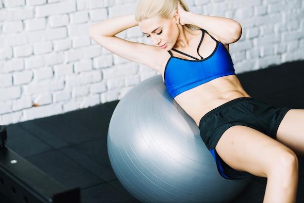 Femme bien bâtie faisant des craquements abdominaux sur fitball