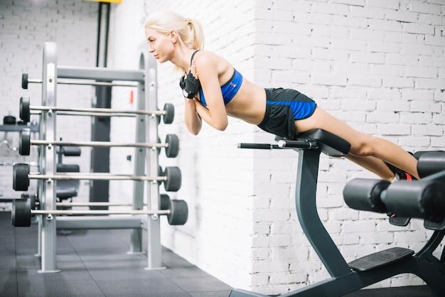 Femme bien bâtie faisant des exercices pour le dos