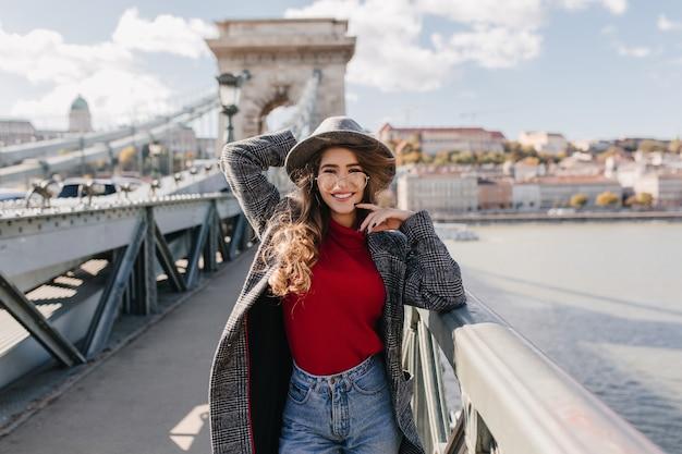 Femme bien habillée dans des verres marchant sur le pont