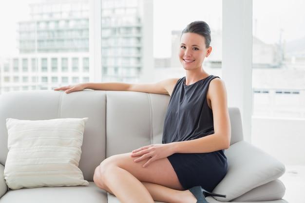 Femme bien habillée souriante assise sur le canapé à la maison