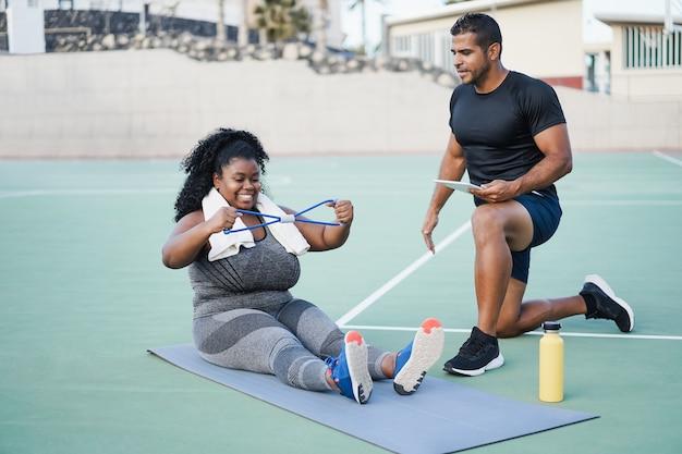 Femme bien roulée et entraîneur personnel faisant une séance d'entraînement en plein air - accent principal sur le visage de la fille