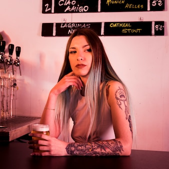 Femme avec de la bière artisanale au bar