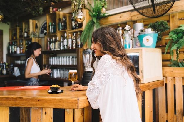 Femme avec de la bière au bar